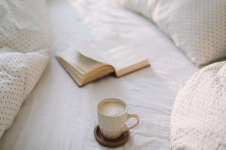 Open book on bedsheets and a cup of coffee. Good morning. Breakfast in bed. flat lay