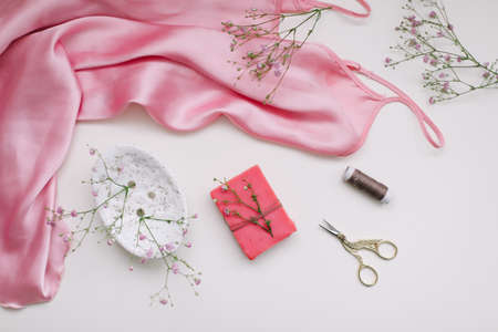 Composition with pink silk fabric, gift in craft paper and threads and scissors on white background. Flat lay, top view. Hobby, leisure concept.