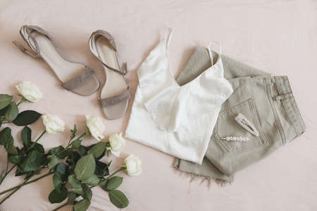Jeans, sandals and bouquet of flowers on beige background. Top view of female casual spring summer outfit. Trendy stylish women clothes. Flat lay