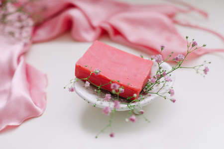 Spa composition with pink soap bar with ceramic soap dish, silk babric and flowers