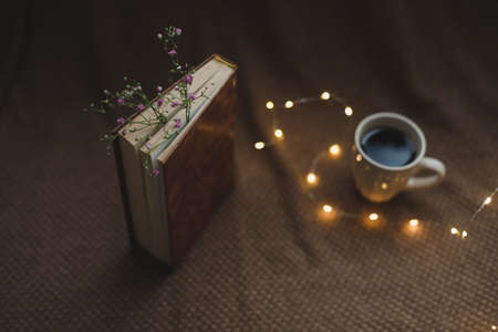 A book with flowers and cup of coffee on dark background top view