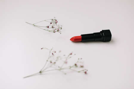 Red lipstick with flowers on white background