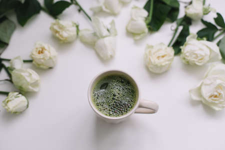 A cup of green matcha tea with white roses on white background view from above. Flatlay, top view, copy space Stock fotó