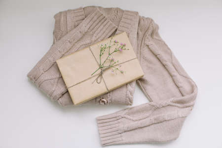 beige knitted sweater with a gift in craft paper top view with copyspace