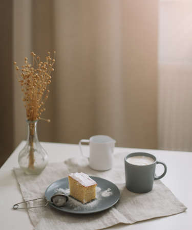 Morning breakfast with a piece of fresh homemade cake, pitcher and cup of coffee on a table