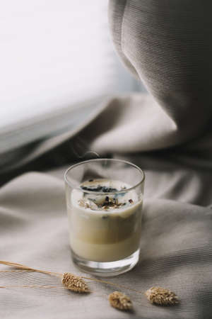 aromatic scented candle with smoke and dried flowers on beige textile background Stock fotó