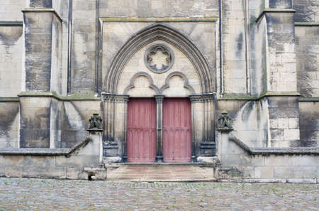 the medieval: Stone portal and a wooden door to the medieval church Troyes, France