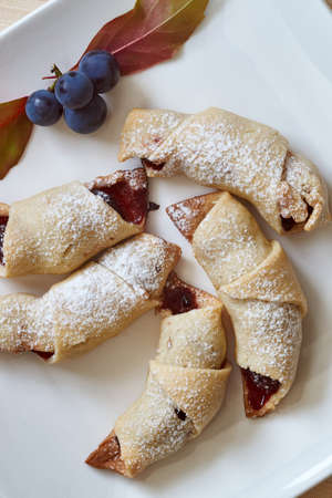 sprinkled: Dessert croissants sprinkled with sugar and stuffed with cherries Stock Photo