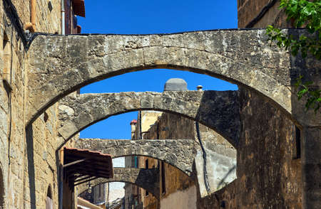arcos de piedra: arcos de piedra en una calle estrecha en la ciudad de Rodas en Grecia Editorial