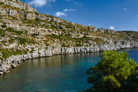 greece shoreline: rocky cliff at the edge of the Mediterranean Sea, on the island of Rhodes