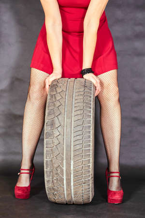 clasp feet: Elegant girl in a red dress holding a car tire