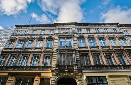 A facade of an Art Nouveau townhouse next to a modernist building in Poznan