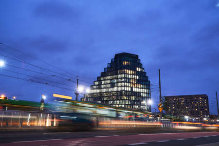 Cars, trams and a modern office building in Poznan in the evening