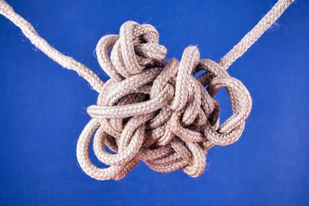 A tangled knot on a rope on a blue background