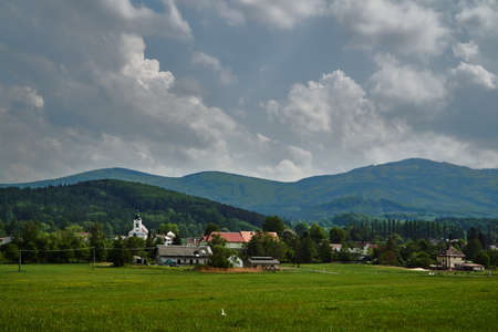 Rural landscape with a church tower and mountain slopes in the Czech Republic
