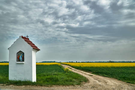 Rural landscape with a roadside chapel and a blooming rapeseed in Poland
