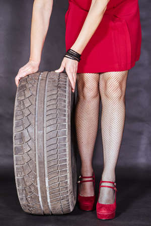 Elegant girl in a red dress holding a car tire