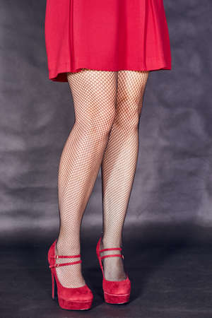 The slim legs of the girl in the red dress