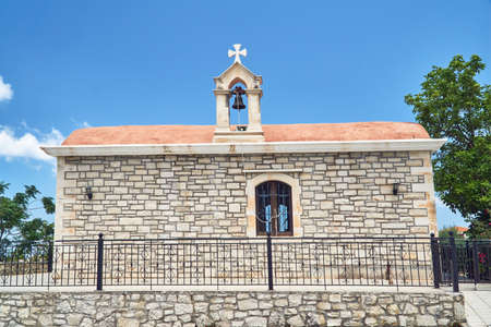A stone Orthodox church with a bell tower on the island of Crete