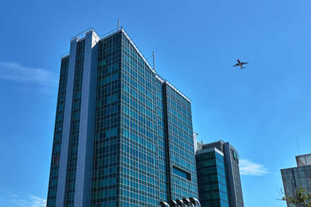 A plane flying over modern office buildings in Poznan