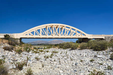 A road arched bridge over a dried river on the island of Rhodes Stock Photo