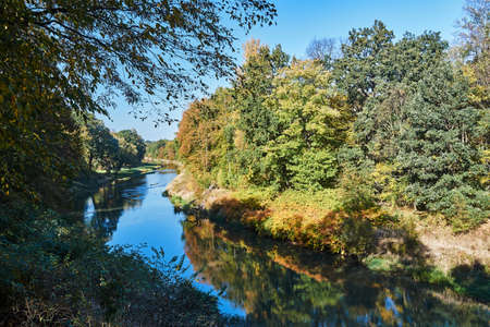 Trees on the banks of the Nysa ?u?ycka during autumn on the border between Poland and Germany Stock Photo