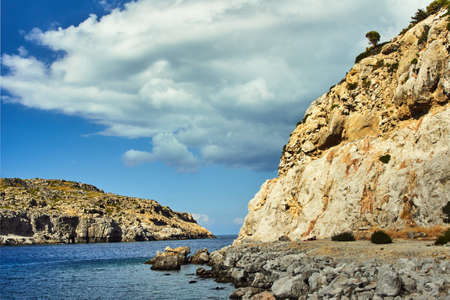 rocky cliff at the edge of the Mediterranean Sea, on the island of Rhodes