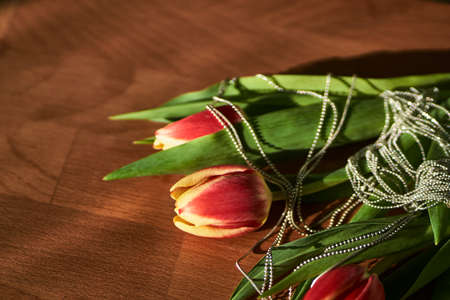 A bouquet of red tulips and a silver chain
