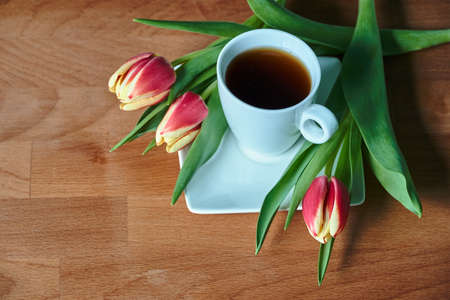 A bouquet of red tulips and a cup with black coffee on a wooden table