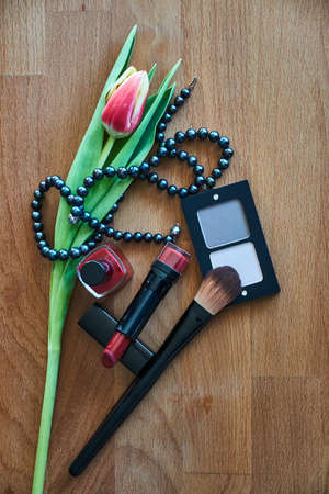 Cosmetics, pearl necklace and tulip on a wooden table
