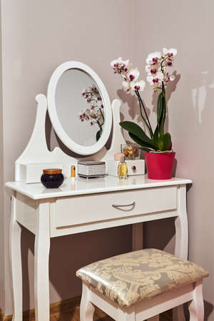 White dressing table with a mirror and a bouquet of flowers