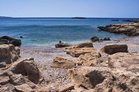 Lonely girl on the rocky coast of the Mediterranean sea on the island of Crete