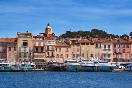 Sailboats and yachts moored to the quay port of Saint-Tropez, France