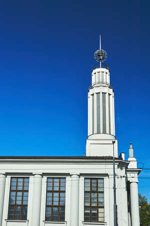 a white, historic modernist building with a tower in Poznan