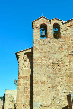 Wall of a stone church with a bell tower in the city of Pitigliano in Italy