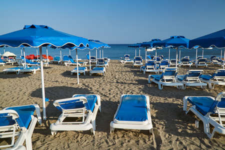Umbrellas and sunbeds on the sandy beach of the Greek island of Rhodes
