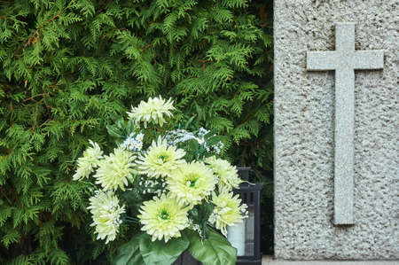 A bouquet of autumn chrysanthemum flowers and a stone cross on a grave