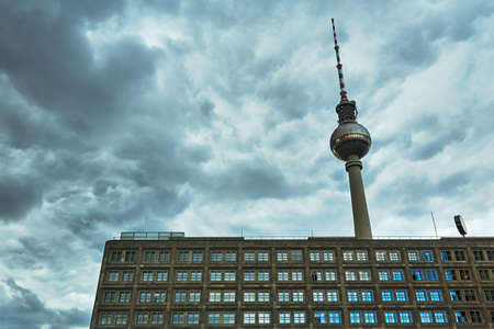 Modernist building and radio and television tower on a cloudy Berlin day