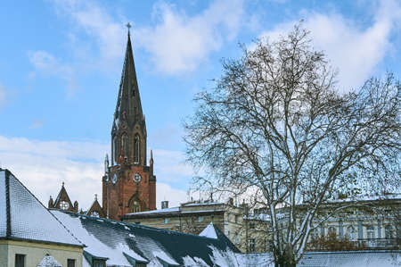 Snow-covered roofs of houses and a tower of a Gothic church in Poznan
