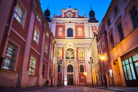 The facade of the baroque church and the cobbled street at night in Poznan