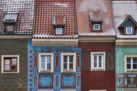 the facade of historic tenement houses in the winter on the market square in Poznan