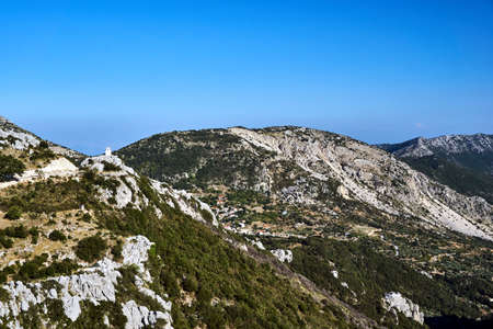 Mountain landscape with rocky peaks and the bell tower of the Orthodox chapel on the island of Lefkada Banque d'images