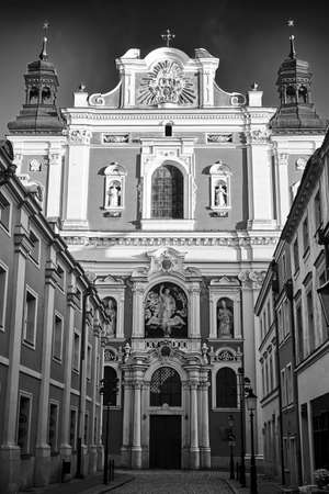 facade of the baroque church decorated with columns and statues in Poznan, black and white