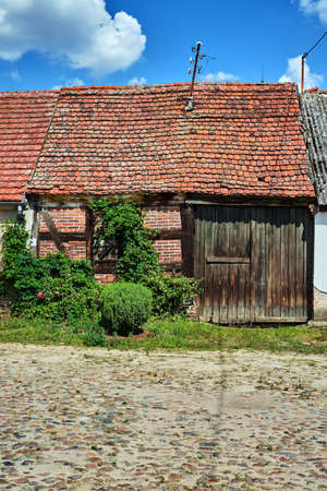 A paved market square and an old house with a wooden gate in the village of Bledzew in Poland