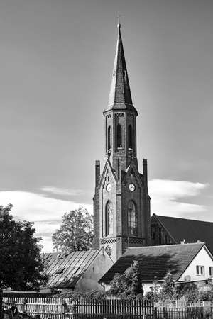 The tower of the historic gothic red brick church in the city of Lubniewice in Poland, black and white