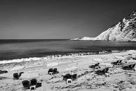 Umbrellas and deck chairs on the sandy beach of Petani Bay on the island of Kefalonia in Greece, monochrome