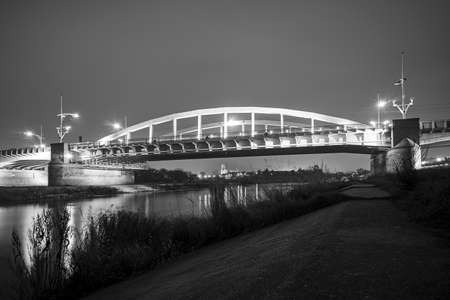 Steel structure of road bridge over the Warta river at night in the city of Poznan, monochrome