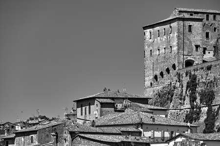 Ancient stone buildings in the town of Sovana, Italy, monochrome