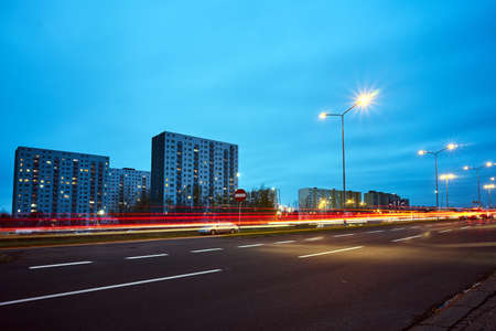 Blocks of flats and a two-lane street during a night in Poznan
