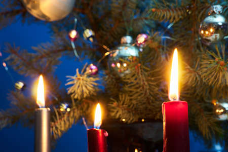 A candle flame on a background of decorated spruce branches of a Christmas tree in Poland